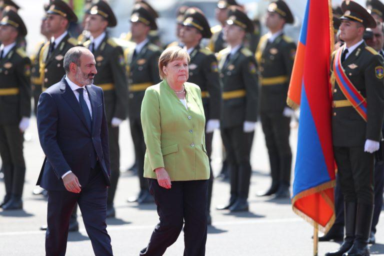 Ősi ellenségek között közvetítene Angela Merkel